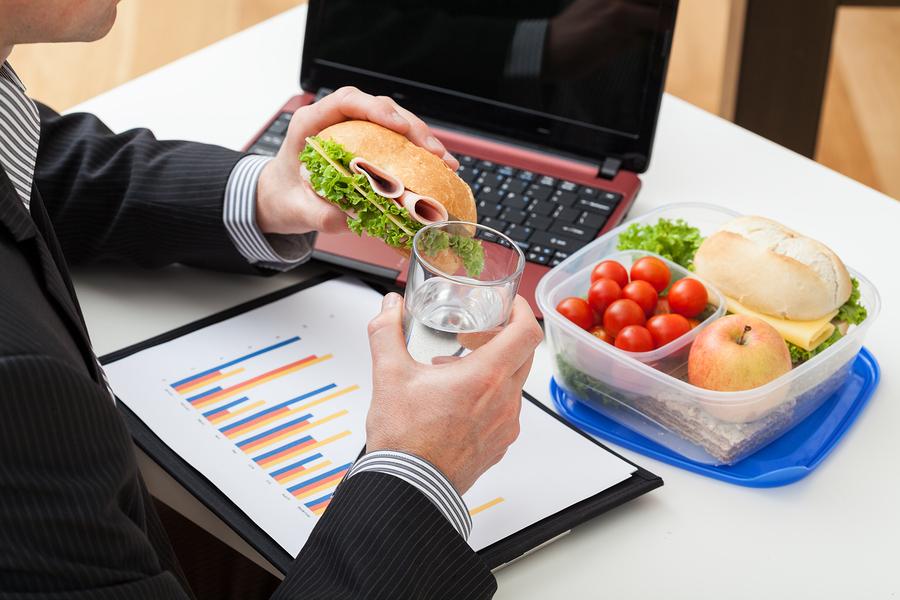 Mann isst bei der Arbeit
