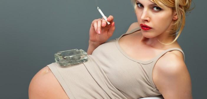 Schwangere Frau raucht Zigarette