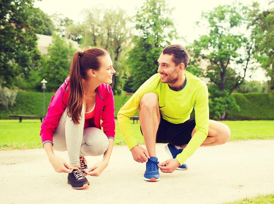 Zwei Personen binden sich Laufschuh zu