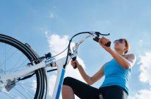 Dame auf E-Bike, von Unten fotografiert, blauer Himmel