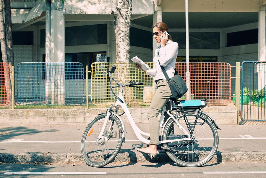 Frau auf E-Bike telefoniert