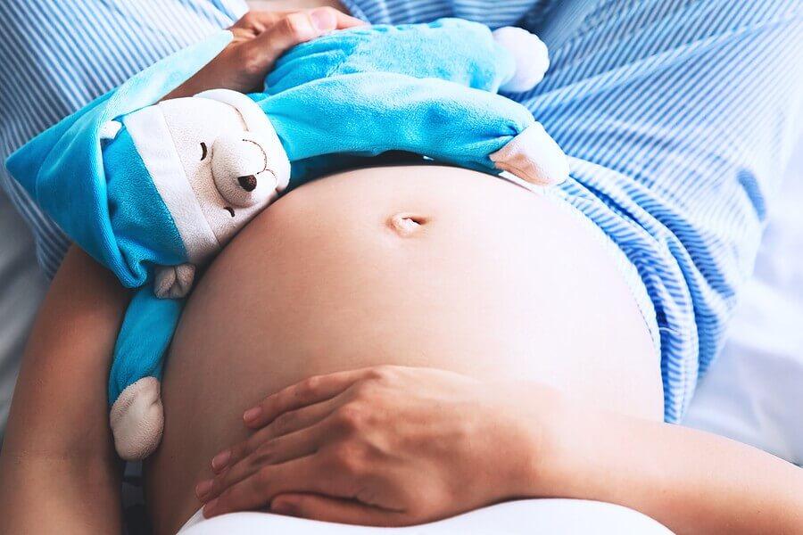 Schwangere Frau die sich auf den Bauch greift.