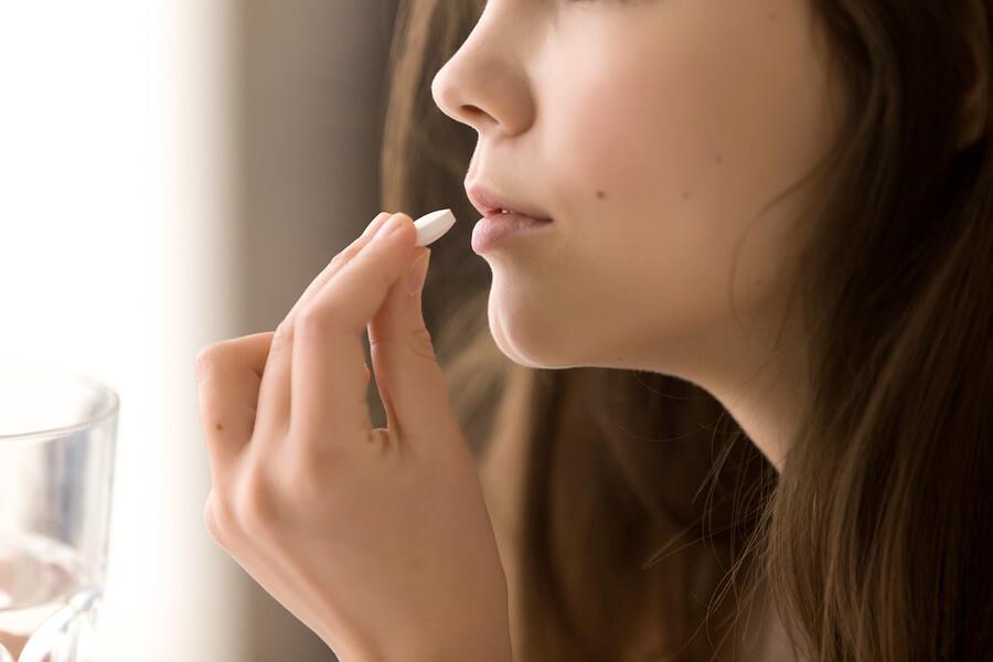 Junge Frau beim Einnehmen der Pille.