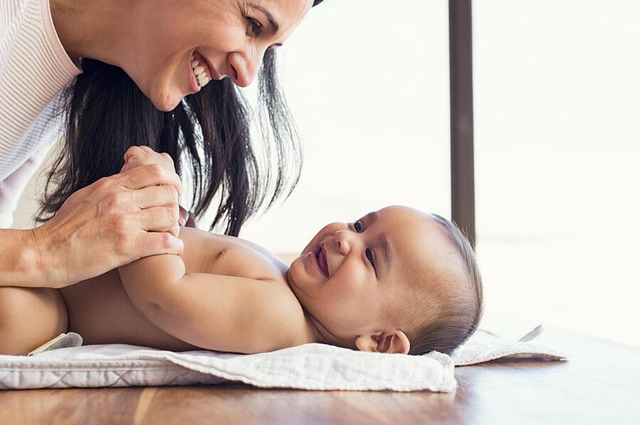 Frau mittleren Alters hat Spaß mit Ihrem fröhlichen Baby.