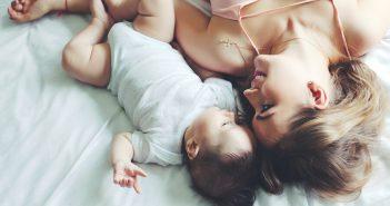 Junge Frau freut sich über ihr gesundes Baby