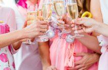 Frauen die eine Babyparty feiern und anstoßen.