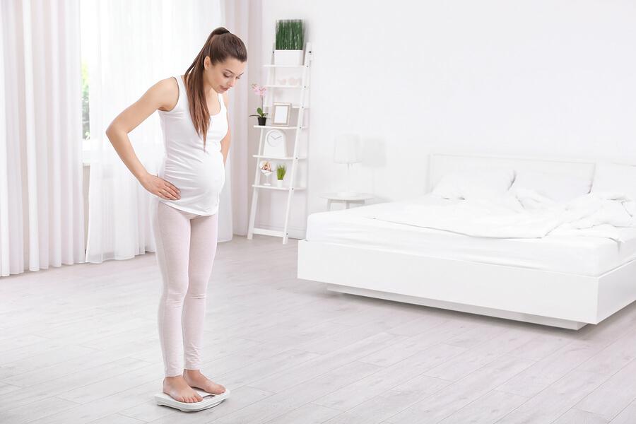 Schwangere Frau stellt sich auf die Waage um ihr Gewicht zu messen.