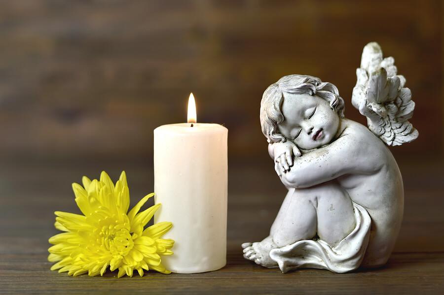 brennende Kerze, Engel sitzt davor