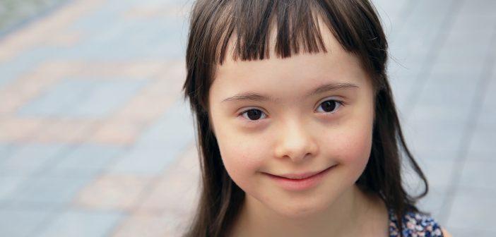 Kleines neugieriges Mädchen mit Down Syndrom.