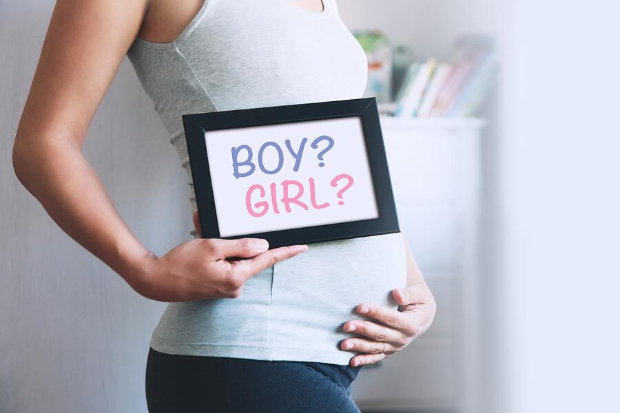 """Bauch einer Schwangeren Frau mit Tafel """"Boy or Girl""""."""